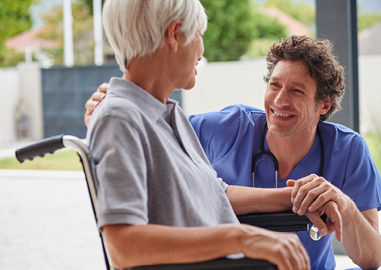 Image of doctor smiling at patient in a wheelchair