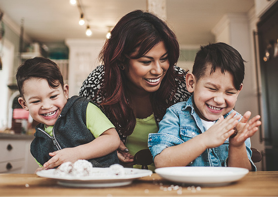 Image of mother and children preparing food together